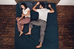 Top view. Young couple is sleeping together on big bed with blue sheet. Couple`s sleep concept. Rest at home. Sleep poses. Sleep poses for couples Royalty Free Stock Photography