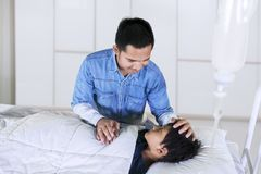 Young father visiting his sick son in hospital stock photography
