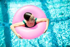 Swimming with buoy. Top view of young female in pink buoy spending time in azure water of swimming-pool royalty free stock image