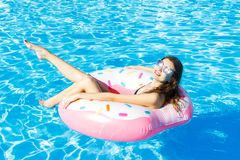 Top view of young female swim with pink circle in pool.  stock photography
