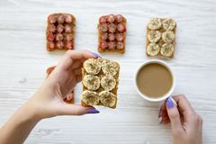 Top view young girl is holding vegan toast and coffee over white wooden background. stock photography