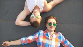 Top view of young happy male couple in sunglasses lying on rooftop of high-rise building and smiling. Handsome gay boys. Looking at camera and enjoying to spend stock video