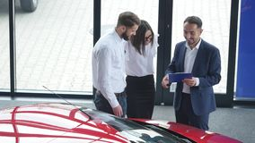 Top view of young male consultant and buyers signing contract for new car in auto show. Concept for car rental stock video