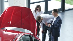 Top view of young male consultant and buyers signing contract for new car in auto show. Concept for car rental stock video footage