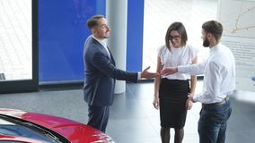 Top view of young male consultant and buyers signing contract for new car in auto show. Concept for car rental