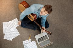 Top view of young man with guitar smiling at camera Royalty Free Stock Images