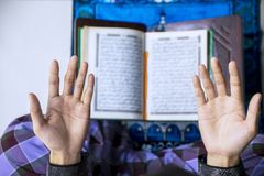 Young man hands praying to the Allah. Top view of young man hands praying to the Allah after reading the Quran stock photography