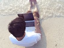 Top view of young man with laptop sitting on sand of tropical beach during sunset in summer time. Relax and travel concept. Top view of young man with laptop Royalty Free Stock Photo
