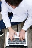 Top view of a young man typing on laptop Royalty Free Stock Images