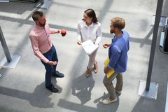 Top view of young modern people in smart casual wear discussing business while standing in creative office. stock photos