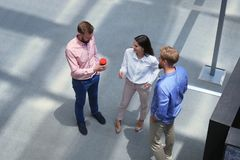 Top view of young modern people in smart casual wear discussing business while standing in creative office. stock images