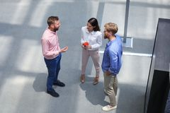 Top view of young modern people in smart casual wear discussing business while standing in creative office. stock image