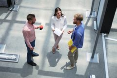 Top view of young modern people in smart casual wear discussing business while standing in creative office. royalty free stock image