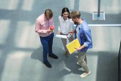 Top view of young modern people in smart casual wear discussing business while standing in creative office. stock photo