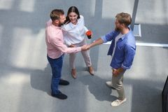 Top view of young modern people in smart casual wear shaking hands standing with their colleagues in creative office. royalty free stock photography