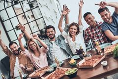 Happy!. Top view of young people in casual wear gesturing and smiling while having a dinner party indoors royalty free stock photo