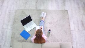 Top view of young pretty woman stufying at home. Top view of young pretty woman studying at home. Attractive female student sitting on carpet at living room stock video