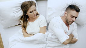 Top view of young upset couple lying in bed have problems after quarrel and angry each other at home stock footage