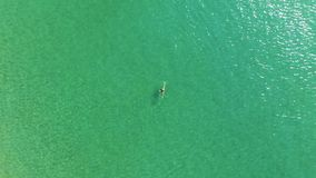 Top view of young woman in bright bikini is swimming in the transparent, blue sea. Aerial view of slim woman floating on stock video footage