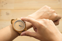 Top view. young woman equip wooden wrist watch on her arm and ch Stock Images