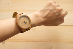 Top view. young woman equip wooden wrist watch on her arm have w Stock Image