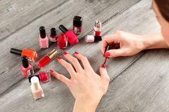 Top view on young woman hands, applying second layer of nail pol Royalty Free Stock Photos