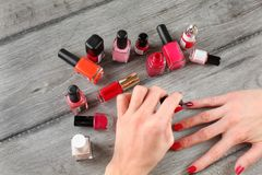 Top view - young woman hands, applying second layer of nail varn Stock Photos