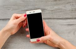 Top view on young woman hands, with red nails, holding white smart phone. Select black screen to add your image or text. stock photos