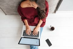 Top view of a young woman holding laptop computer. On her lap while sitting at home Stock Photos