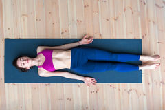 Top view of young woman lying in corpse or dead body pose relaxing after practicing yoga Stock Image