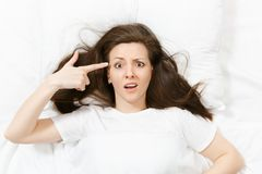 Top view young woman point fingers to head as if she about shoot herself, lying in bed with white sheet, pillow, blanket stock image