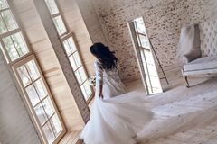 Dancing queen. Top view of young woman in silk bathrobe trying on her wedding dress while standing near window Royalty Free Stock Photography