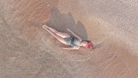 Top view young woman in a swimsuit lying on a sandy beach her body caressing the surf