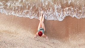 Top view young woman in a swimsuit sitting on a sandy beach her legs caressing the surf stock video footage