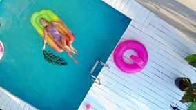 Top view young woman in swimsuit swims in pool on air mattress. Drone shot stock video footage