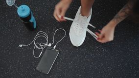 Top View Young woman tying shoelaces on floor, top view. Ready for gym workout phone headphones cell mobile water girl. Young woman tying shoelaces on floor stock video footage