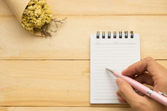 Top view. young woman using hand for writing on empty notebook p Stock Images