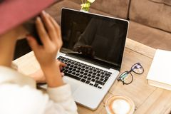 Top view of young woman using laptop while talking on mobile phone, royalty free stock images
