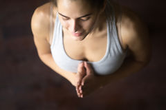 Top view of young woman in yoga pose with Namaste. Close up portrait of beautiful young happy model girl working out at home, doing yoga exercise, standing in stock photography