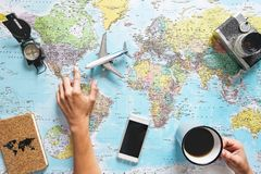 Top view of young woman planning her vacation using world map while drinking coffee - Tourist pointing the next travel destination stock photography