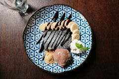 Top view, yummy desserts, a brownie, fresh slice banana, whipped cream and chocolate ice-cream topped with chocolate sauce. And placed in blue dish on wooden Stock Image