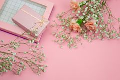 Pink gift box and flowers on a pastel pink background. Top view pink gift box and flowers on a pastel pink background stock images