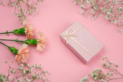 Pink gift box and flowers on a pastel pink background. Top view pink gift box and flowers on a pastel pink background royalty free stock image