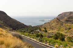 Top views of Agaete fishing town from mountain in Gran Canaria, Spain. Road leading to Puerto de las Nieves in Canary Islands. Harbor, canyon, valley, natural royalty free stock photo