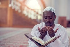 Top viewv of African Muslim Man Making Traditional Prayer To God While Wearing A Traditional Cap Dishdasha.  royalty free stock photo