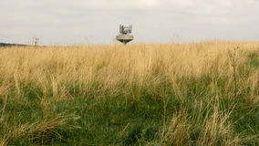 Top of the water tank with radio transmitters in the grass field. A water tank with radio transmitters on the horizon of the dry grass field stock photo