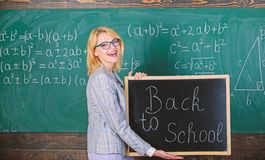 Top ways to welcome students back to school. Teacher woman hold blackboard inscription back to school. It is school time. Again. School teacher happy welcome royalty free stock image