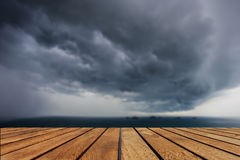 Top of wood table and dark clouds over the sea Royalty Free Stock Photo
