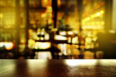 Top of wood table with light reflection with blur pub club or ba. Top of wood table with light reflection with blur abstract pub club or bar light in the dark Royalty Free Stock Image