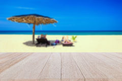 Top wooden table and blur of tropical beach background Stock Images